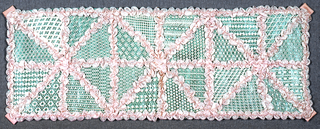 Net embroidered in twenty-four different patterns, edged with pink silk ribbon and backed with glazed green paper
