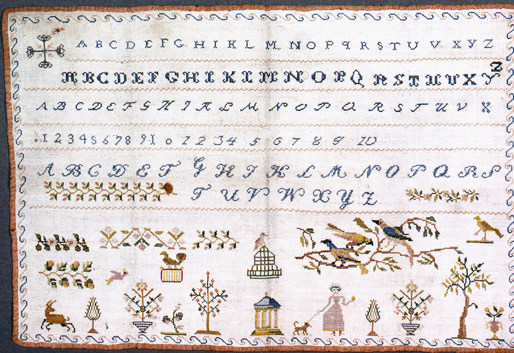 Alphabets, numerals, birds, plants, people all surrounded by a border of scrolls.  Bound with pink silk ribbon.