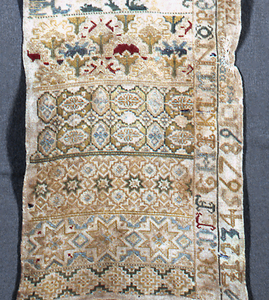 Sampler divided into horizontal bands showing birds, Crucifixion, animals, floral and geometric borders.  In compartments on one side, alphabets, numerals and crowns.