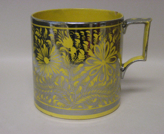 Cylindrical form with squared loop handle; yellow ground with silver luster decoration of flower and foliate forms; silver bands at mouth, foot, and on handle. Yellow interior.