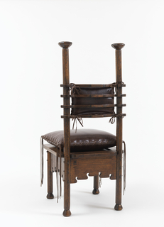 High-backed side chair; oak frame composed of two posts culminating in octagonal stiles at top; seat back of four curved horizontal elements. Square seat with slit cut in top rear; apron with curved bottom edges incorporating notch. Four legs ending in eight-sided bun feet. Replacement cushions of dark brown leather with leather lanyards at corners; rectangular back cushion tied to horizontal elements of chair frame; square seat cushion rests on seat, multiple lanyards at each corner hanging to floor.