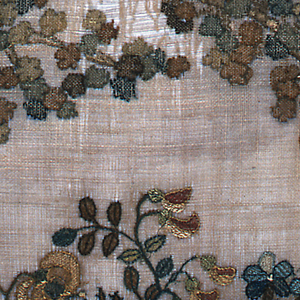 Basket of flowers under an arch of two stout trees, each growing from a low mound. Panel at bottom has four darned squares on each side of the panel with a darning cross in the middle. Dinah (?) Phillips written in dark brown.