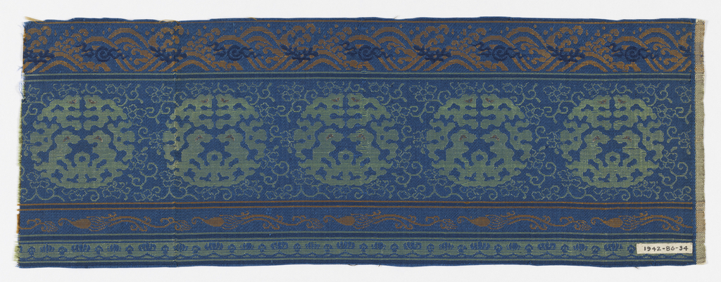 Blue background with central motif of green roundels with gold and green vines. Top border of orange and blue waves. Bottom border with orange flowers and green shells.