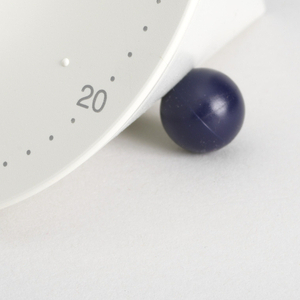 White conical form oriented on its side, balanced on one side by by a small dark purple ball and on the other by a lozenge-shaped foot; circular face with gray numerals printed around edge; white semicircular dial in center.