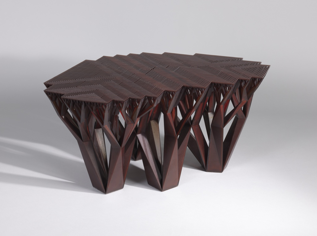 Irregular, low, transluscent brown table comprising angular and linear elements suggestive of a grove of four trees, the base reminiscent of the trunks and branches, the flat open-work top evoking the trees' leafy foliage.