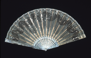 Pleated fan. White gauze leaf embroidered with silver spangles in the form of thick swags. Pierced and piquéd mother-of-pearl sticks.