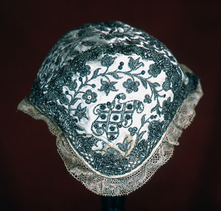 Infant's cap of white satin embroidered with silver metallic yarns and spangles and trimmed with silver bobbin lace. Pattern has a flowering vine and an amorphous shape filled with a lattice. Bobbin lace edging and blue lining.