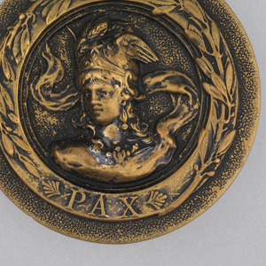 "Circular button with bust of woman (?) in helmet and armor; ""PAX"" under figure, within band around rim.