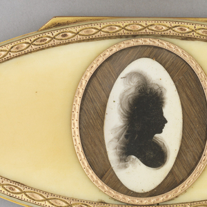 Horizontally oriented ovoid form; brown with gold border surround; on lid, central circular panel with silhouette of woman facing inprofile, facing left. Two additional silhouettes on inner cover and on box.