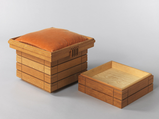 Upright rectangular form composed of stacked shallow plywood boxes; the top box designed as seat, with well to accept removeable cushion.  Band of molding and five applied vertical wood strips decorate each side of seat; lower sections have incised linear decoration at corners.  Sections can be stacked to make stool of varying height.  Seat section designed to serve as galleried tray when cushion removed.