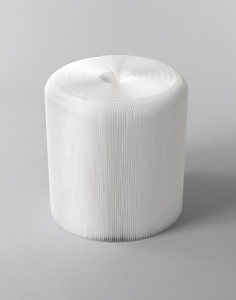 Collapsible stool composed of white polyethylene sheets joined to form cylindrical honeycombed structure (polyethylene sandwiched between two white cardboard sheets each with three embedded magnets that link to form cylinder; cardboard sheets can be separated so structure collapses into a rectangular block for storage).