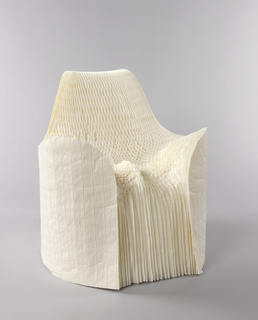 Roughly cylindrical form of thin paper layers fanned out to form chair; the front and top cut and shaped to form contoured seat, low arms, and back, the seat further compressed and contoured by designer sitting in chair.