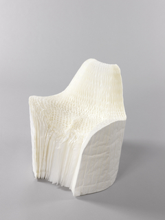 Roughly cylindrical form of thin paper layers fanned out to form chair; the front and top cut and shaped to form contoured seat, low arms, and back, the seat further compressed and contoured by someone sitting in chair.
