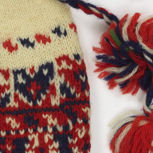 Bag knitted in stockinette stitch, with a drawstring at the top; now open at bottom. Deep band of decoration in red and blue on a white ground. Three tassels attached to the bottom. Red, white and blue plaited cord at top, ending in two tassels.