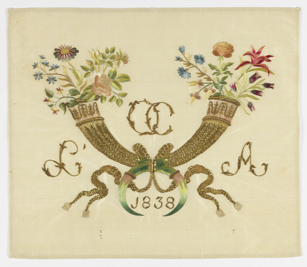 """Two crossed horns with flowers springing from the top. Horns in gold with tips in silk. Flowers in silk. Between horns at top are initials in gold: """"OC"""". At left: """"L"""" and at right: """"A"""". Between tips of horns: """"1838""""."""