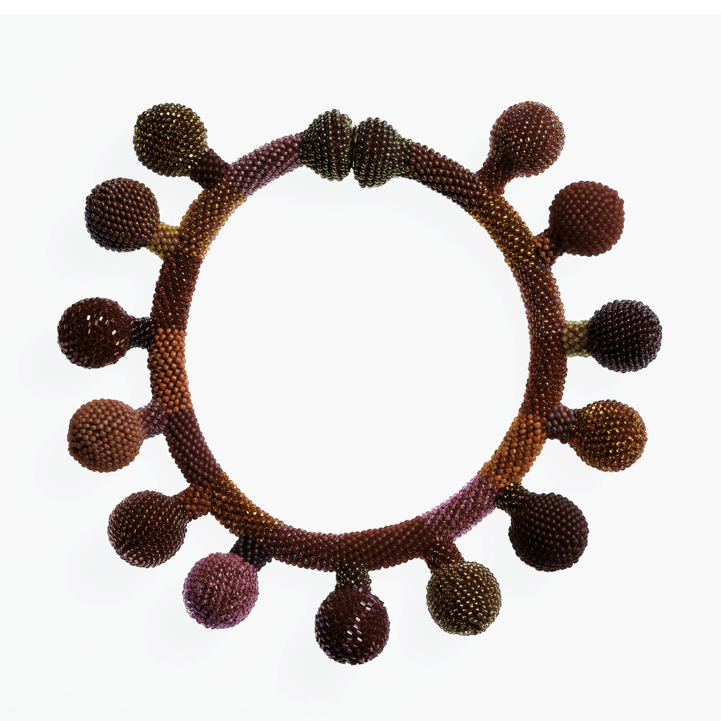 Glass-beaded necklace in form of circular band with projecting balls, all in red, orange and gold tones. Large metal snap closure at back.