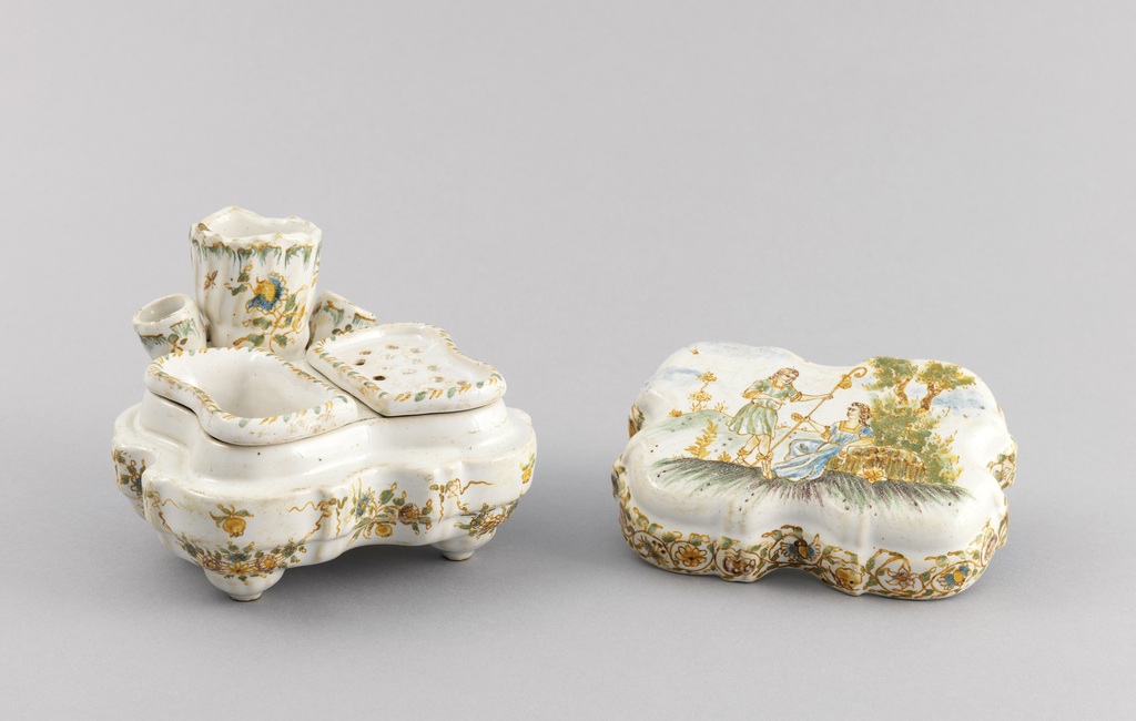 Inkstand composed of quatrefoil-shaped body (a) with three conical projections at back center (to hold writing implements?); base with four short conical feet; white ground decorated with yellow, blue and green flowers and garlands. Quatrefoil-shaped lid (b) showing allegorical scene of shepherds with foliage-scroll borders. Interior inset with two shaped containers (c,d), with yellow, blue and green decoration; one container with pierced top.