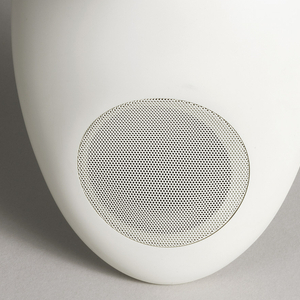 """White, contoured ovoid form suggestive of a face; round speaker forming """"mouth""""; station number indicator at upper right forming """"eye."""" Control dials on back; antenna cord trailing from lower right. Indentation for wall mount on back."""