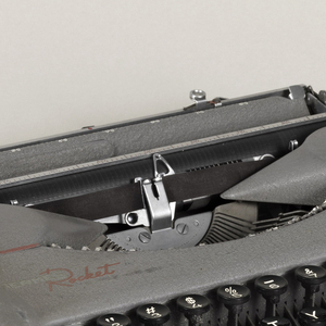 Rectangular grey typewriter with rounded corners; flat base, black keys with white letters and numbers; gray case with handle.