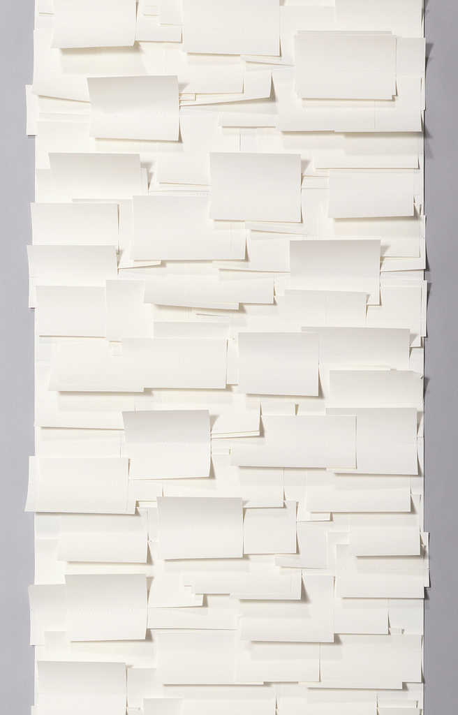 This paper is composed of small overlapping rectangles of white paper in varying sizes sewn onto a white paper backing.  These squares are sewn in horizontal rows evenly spaced several inches apart.