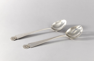 """Part of a pair of salad servers. Spoon has leaf-shaped bowl and monogram applied on pentagonal terminal: """"PN""""."""