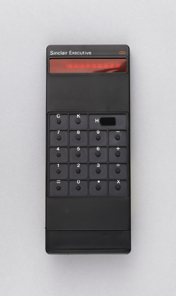 """Black rectangular calculator with small round buttons in sunken squares, white letters and numbers. Above, red screen and in white: """"Sinclair Executive."""""""