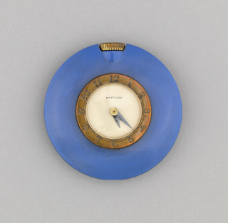 """Circular form; smooth blue case surrounding brass(?) band with black numerals encircling white face with black hands; brass(?) stem at top. At center: """"WESTCLOX""""."""
