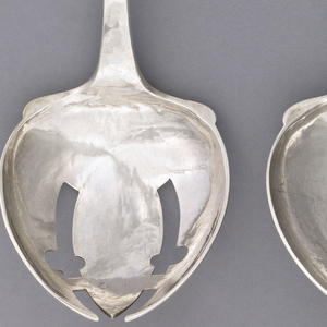 """Part of a pair of salad servers. Fork has leaf-shaped bowl and monogram applied on pentagonal terminal: """"PN""""; like spoon but slotted and open."""