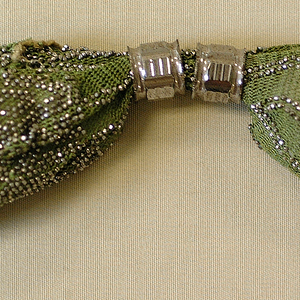 Soft green colored crocheted silk ornamented with cut steel beads in diamond pattern. Two hexagonal rings of cut steel control side closing. Cut steel drops, in faceted ball shape, at each end.