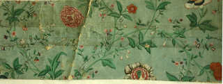 Horizontal rectangle. Irregular serpentine intertwined vines, with morning-glory, lotus and other flowers, painted in colors on green ground.