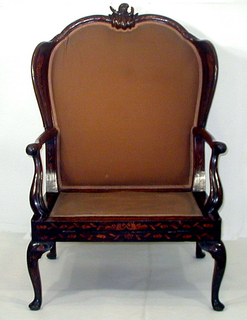 Double arched top rail, crested with a complex of scrolls.  Wood wings rest on slightly curved arms which are supported by curved channeled  stumps.   Flat seat framing.  Cabriole front and rear legs.  Chair inlaid on all surfaces with floral designs.  Unfolds to form bed.