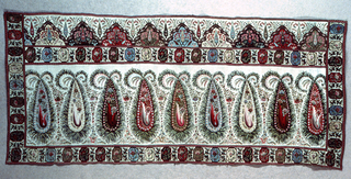 A shawl border with a horizontal row of large stylized decorated cones with leafy edges; broad guard border on four sides consisting of octagonal medallions, each framing a floral spray, and oak leaves between. Broad border at the top with a row of decorated mounds with flowery sprays growing on and in them. Small cypress shape in center of each and between each. In a great variety of colors on white ground.