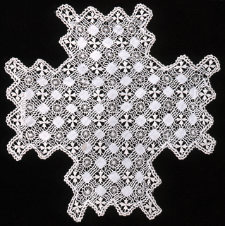 Drawn work doily in the shape of a cross with geometric filling stitches.