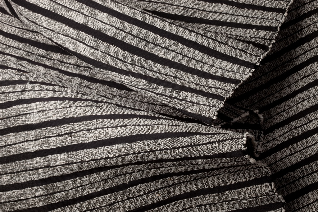 Narrow width of heavy fabric with a black ground and stripes of kibiso fiber.