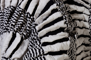Width of fabric gathered into deep folds to make narrow, highly elastic piece, white with bands of narrow black and white stripes.