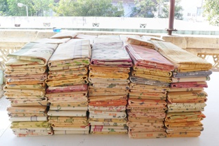 Stack of folded jamdani saris of sheer brocaded cotton in soft pastel colors.