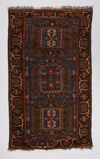 "Prayer-rug sized carpet with dark blue ground, field and border layout, knotted fringe. The field and border both include traditional medallion and floral motifs along with weaponry, including tanks and ""butterfly"" landmines."