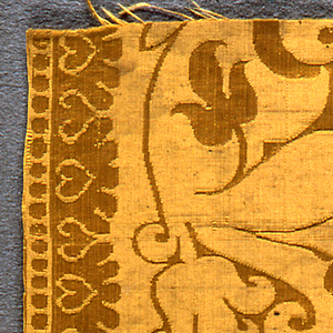 Fragment of yellow silk with a symmetrical design of pomegranates and organic scrolls, with a border along the two sides.