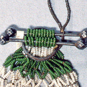 Bag made of fine white and green beads strung in a diamond-shaped net pattern. Attached and held open at top by two bars of steel with cut steel knobs. Cut steel ring allows bars to slide through to open and close bag. Cut steel and gold-colored beads ornament bag at crossing points of net.