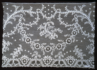 Border with a spray of foliage surrounded by garlands of medallions and floral sprays in symmetric design.  Pattern outlined by cordonnet.