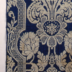 The pattern is white on a blue background and has a symmetrical design of flowers between lattice-like bands on either side.