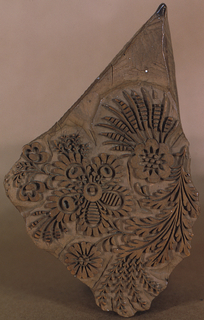 Triangular-shaped block for printing textiles carved in design of conventionalized flowers and leaves on curving stems. Grooves in sides for handling.