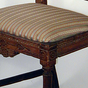 Rectangular open back, the top rail carved with a design of grapes.  Splat composed of five splints, inward-curving and fused centrally.  Straight moulded seat rails, the front grape-carved.