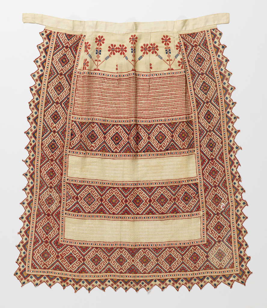 White linen apron with drawnwork and embroidery in colored cotton.