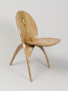 Foldable chair of plywood carved so as to create a striated pattern. Comprised of two interlocking parts so that when folded the chair's volume reduces by half
