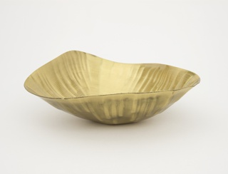 Roughly triangular bowl showing indentations from the pathway of the robotic arm as it moved along its programmed path to transform the flat sheet of brass into a three-dimensional shape.