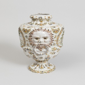 One of pair. Floral swag and posy decoration, cartouches with mythical scenes of figures and animals in landscapes. Bearded mascaron with faux bail handle in mouth in sculptural relief on sides. Creamy glaze.