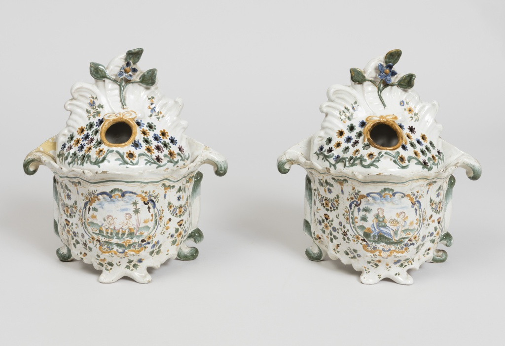 One of a pair. Tureen-form bulb pot with cartouches and green and gold floral decoration; rococo upper body pierced with bulb hole.