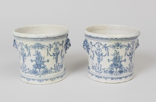 One of a pair. Berainesque blue decoration with molded mascaron at sides.