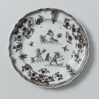 Circular plate with scalloped edge; dark green flora and fauna decoration, three grotesque-type figures in center. Blue-green tinted glaze.